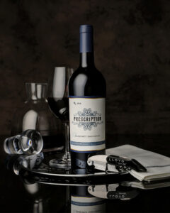 bottle of Cabernet Sauvignon with a glass of wine and wine service accessories