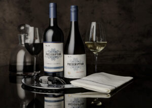 a bottle of Cabernet Sauvignon and a bottle of Chardonnay from Prescription Vineyards, along with glasses and assorted wine accessories.