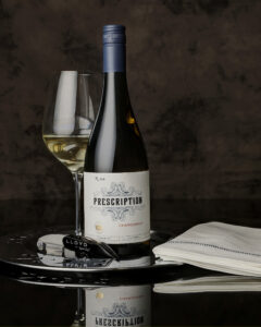 bottle of Chardonnay with a glass of wine and wine service accessories